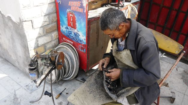 Repairing my shoes by the roadside in Sichuan