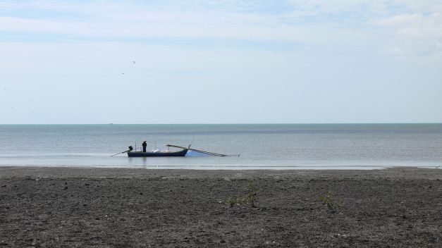 A lone fisherman sets his nets at low tide